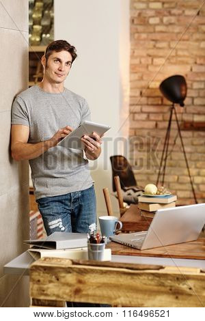 Casual man using tablet computer at home, leaning against wall, looking away.