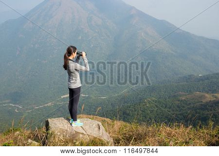 Woman looking though binoculars at mountain