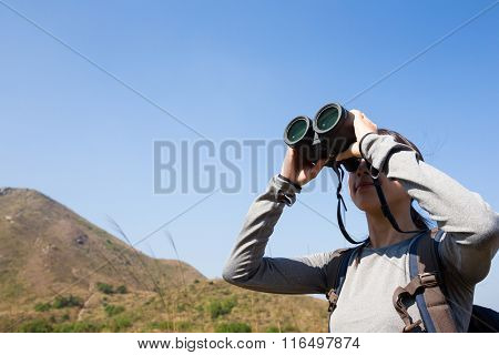 Woman looking through binoculars in mountain