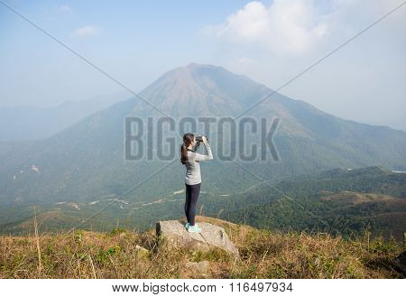 Girl looking though binoculars at hill