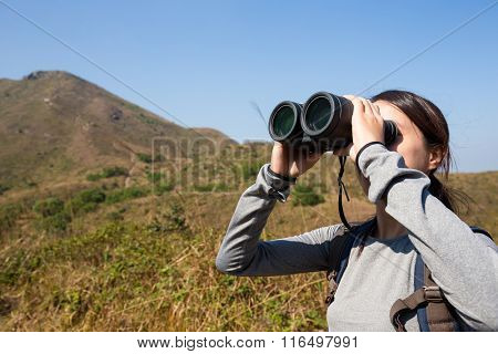 Girl looking through binoculars in mountain