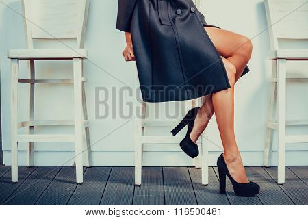 Young woman with black high heels shoes sitting on a chair and crossed her legs, sitting on chair