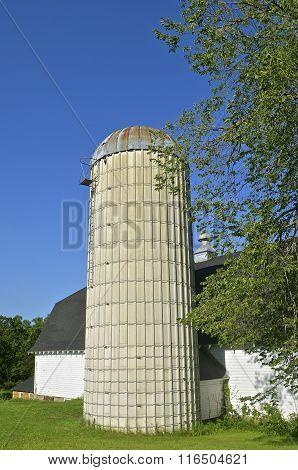 Old concrete silo alongside of a barn