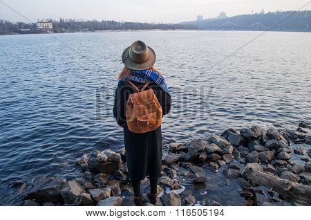 Young woman in hat and with rucksack standing on the riverbank, looking at sunset or sunrise horizon