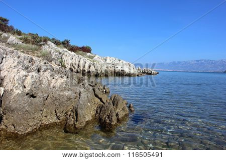 Rocky wild seashore with transparent water