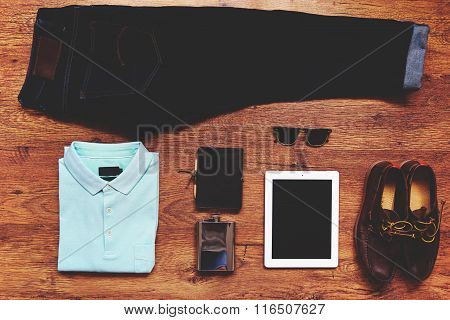 Top view of hipster guy's personal stuff on wooden background