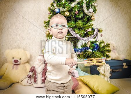 Vintage Portrait Of Little Sad Looking Kid With Rattle Near New Year Fir