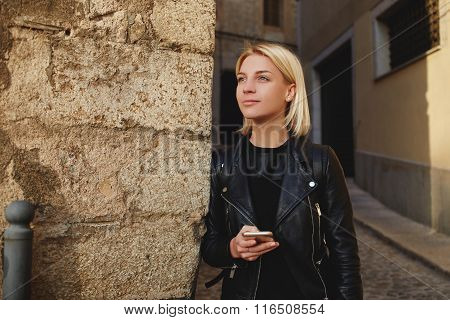 Hipster girl thinking about something while waiting for text message answer on her mobile phone