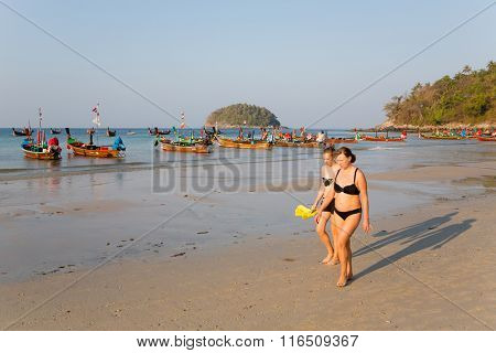 KATA BEACH, THAILAND - CIRCA FEBRUARY, 2015:  People in the early morning on the beach of Kata. This is one of the most popular beaches among tourists in Phuket.