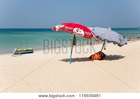 KARON BEACH, THAILAND - CIRCA FEBRUARY, 2015: Umbrellas and tourists rest on Karon beach. This is one of the most popular beaches among tourists in Phuket.