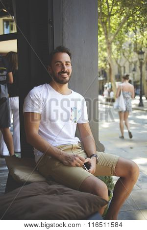 Happy rich male with cell telephone in hand enjoying life while sitting on cafe's windowsill