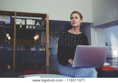 Young thoughtful businesswoman ponders something while holding on her knees open laptop computer
