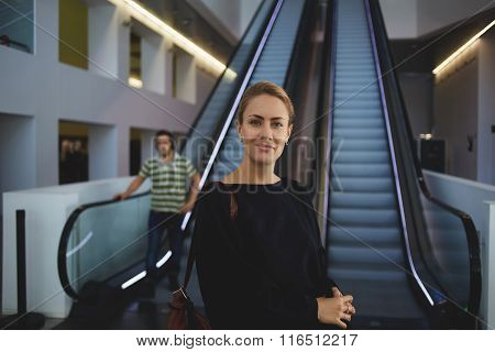 Female confident worker standing near escalator in airport before her business trip overseas