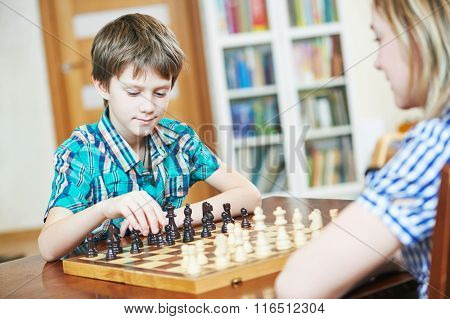 boy playing chess at home