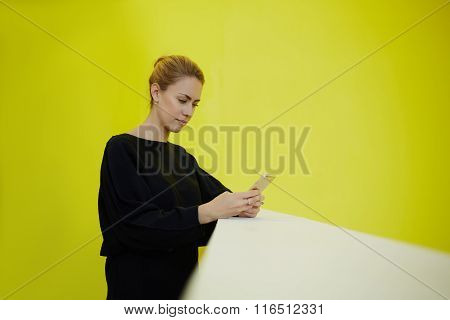 Successful woman financier using cell telephone for counting data during work break