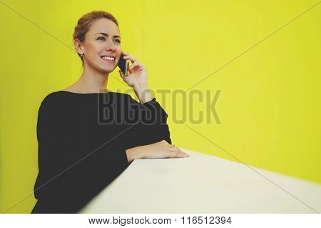 Happy female director talking on mobile phone during break