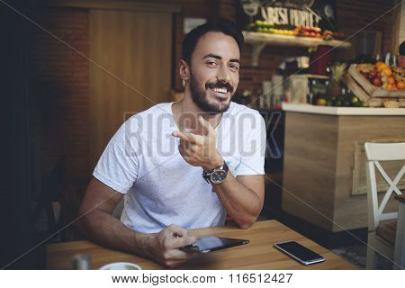 Cheerful confident businessman holding portable touch pad and shows a finger at his coffee shop room