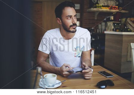 Rich male holding digital tablet and looking for someone during work break in cafe