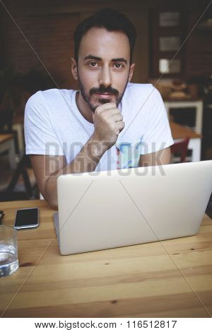 Young handsome man entrepreneur posing while sitting with open laptop computer in his coffee shop