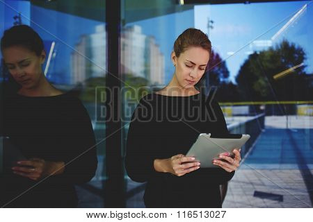 Woman CEO concentrated reading response about company via digital tablet while standing outdoors