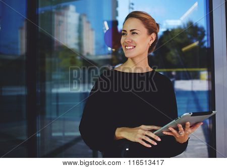 Skilled female manager hold digital tablet and smiling to someone during rest after conference