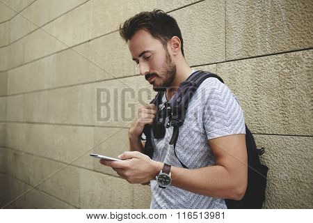 Male traveler awaiting answer on his message on cell telephone during break between walking