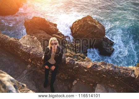 Young female tourist resting after walking while standing near ocean in warm autumn day