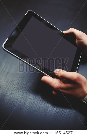 Young businessman working on touch pad against black wooden desktop