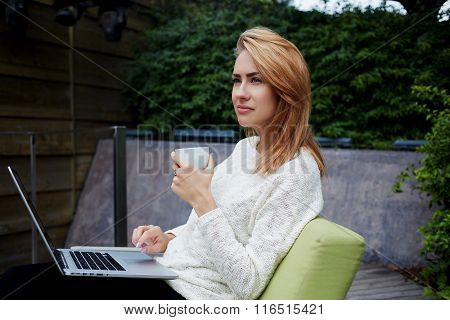 Thoughtful female holding cup of tea while sitting with laptop computer in sidewalk cafe