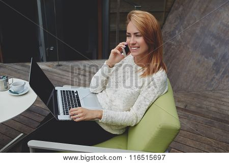 Happy female talking on cell telephone while sitting with laptop computer in cozy cafe