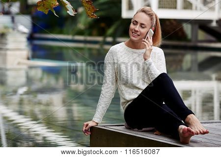 Cheerful female phoning on mobile phone while resting on a wooden pier in beautiful modern park