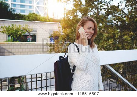Young attractive woman tourist talk on mobile phone while standing on street in spring day
