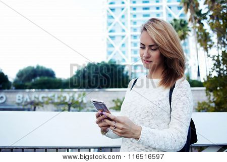 Charming woman watching video on cell telephone while waiting her friend outdoors