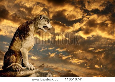 Beautiful sunset, ancient lion statue and storm sky