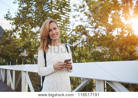 Portrait of smiling woman with mobile phone posing while standing on bridge in spring day
