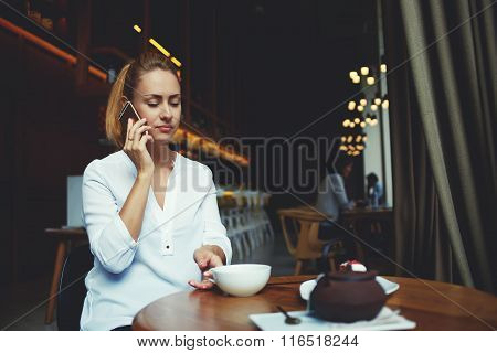 Cute woman calling via mobile phone to her friend which she is waiting in a comfortable restaurant