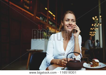 Happy female talking on mobile phone while sitting with sweet desert in cozy cafe