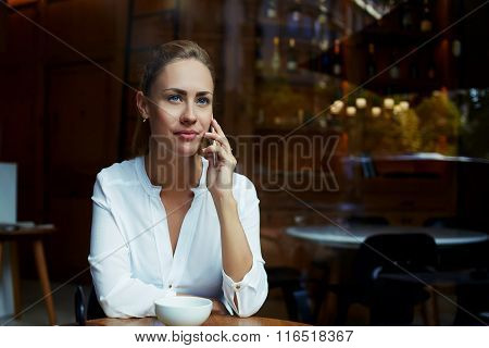 Female entrepreneur talk on smart phone with her parthner during coffee break in restaurant