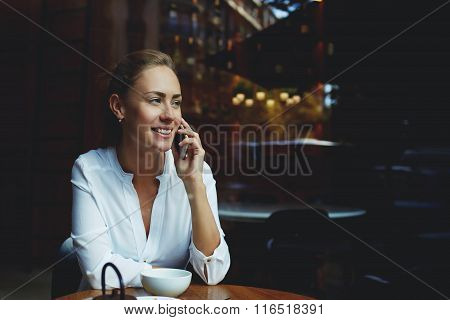 Smiling businesswoman having nice cell telephone conversation during work break in cafe