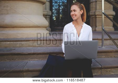 Beautiful woman smiling to someone during work on laptop computer outside in spring day