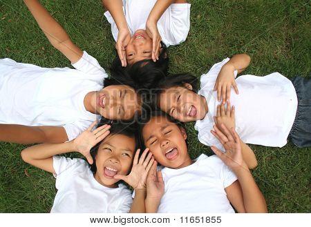 Cinco niños jugando en el parque.