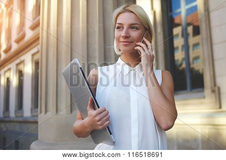 Female student with closed net-book in hand talk on mobile phone while standing near University