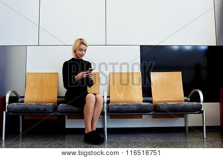 Charming female dressed in black dress chatting on cell telephone during work break in hallway