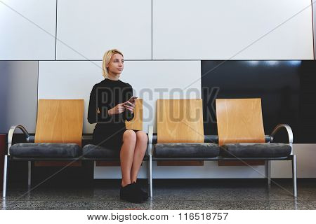 Young thougfull woman thinking about something good while sitting on the bench in office