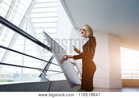 Confident businesswoman holding cell telephone while type information on modern advanced technology