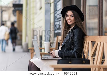 Stylish female holding mobile phone while sitting with laptop computer on cozy bench outside