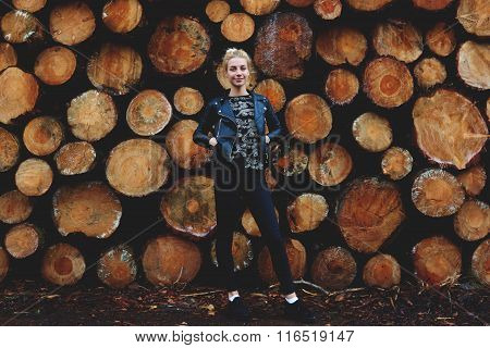 Full length portrait of cute hipster girl posing against cut tree trunks background in autumn day