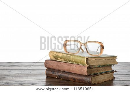 Old Book And Eyeglasses On A Table With Isolated Background