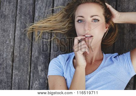 Closely image of a gorgeous woman looks seductively at the camera while lying on a wooden floor