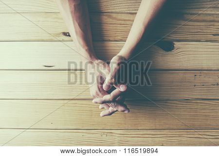 Close up on female hands folded in prayer at a wooden table